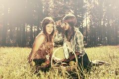 Los jóvenes felices forman a muchachas con una cesta de fruta en la naturaleza Fotos de archivo