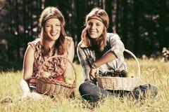 Los jóvenes felices forman a muchachas con una cesta de fruta en la naturaleza Imagenes de archivo