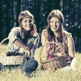 Los jóvenes felices forman a muchachas con una cesta de fruta en la naturaleza Imágenes de archivo libres de regalías