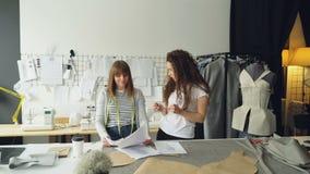 Los jóvenes forman el diseño de empresarios están discutiendo bosquejos de la nueva colección de la ropa en su estudio ligero Las metrajes