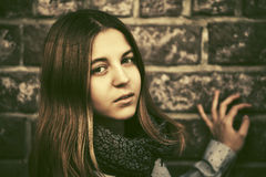 Los jóvenes forman a la muchacha adolescente en la pared de ladrillo Fotografía de archivo libre de regalías