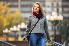 Los jóvenes forman a la mujer rubia que camina en la calle de la ciudad Fotos de archivo
