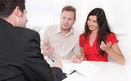 Los jóvenes fusionaron a la pareja en el escritorio en una reunión de negocios Imagenes de archivo