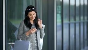 Los jóvenes hermosos forman a la mujer con la ventana cercana de la tienda de los panieres que llama el teléfono elegante metrajes