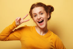 Los jóvenes hermosos sorprendieron a la mujer del redhair sobre fondo amarillo fotos de archivo
