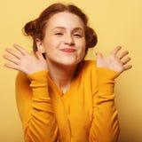 Los jóvenes hermosos sorprendieron a la mujer del redhair sobre fondo amarillo imagenes de archivo