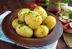Los jóvenes hirvieron las patatas con mantequilla y eneldo en un cuenco de la arcilla Fotografía de archivo
