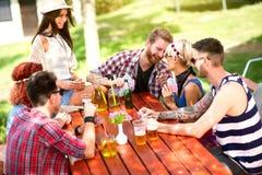 Los jóvenes juegan a las tarjetas, riendo y bromeando en naturaleza foto de archivo libre de regalías