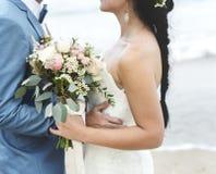 Los jóvenes juntan conseguir casados en la playa Foto de archivo