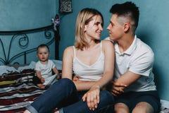 Los jóvenes juntan el abrazo, hija del bebé en el fondo imagen de archivo libre de regalías