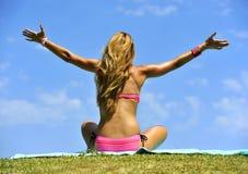 Los jóvenes liberan a la mujer rubia atractiva en brazos rosados de la abertura del bikini al cielo Imagen de archivo libre de regalías