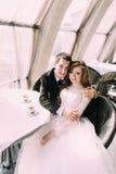 Los jóvenes lindos casados juntan el abrazo de sentarse en cafetería y de mirar la cámara foto de archivo