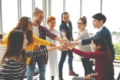 Los jóvenes multiétnicos combinan las manos de la pila juntas como la unidad y trabajo en equipo en oficina moderna Colaboración  imagen de archivo libre de regalías