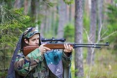 Los jóvenes reclutan con el rifle óptico en bosque Imagen de archivo