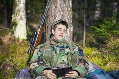 Los jóvenes reclutan con el rifle óptico en bosque Imágenes de archivo libres de regalías