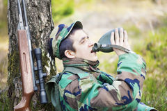 Los jóvenes reclutan con el rifle óptico en bosque Fotografía de archivo libre de regalías