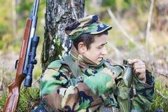 Los jóvenes reclutan con el rifle óptico en bosque Fotografía de archivo