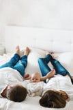Los jóvenes se juntan con el pequeño niño en la cama blanca El niño está mirando la cámara Imagen de archivo libre de regalías