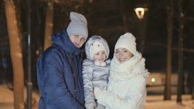 Los jóvenes se juntan con los pequeños abrazos de la hija y los besos en invierno de la noche parquean almacen de metraje de vídeo