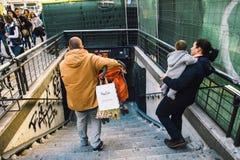 Los jóvenes se juntan con los pequeños niños que descienden las escaleras Foto de archivo libre de regalías