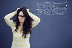 Los jóvenes sorprendieron a la mujer en fondo del gris azul con los gráficos de la matemáticas foto de archivo libre de regalías
