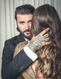 Los jóvenes tatuaron el retrato del hombre vestido elegante abrazando un rubio Fotos de archivo