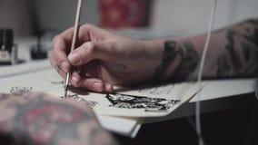 Los jóvenes tatuaron a la mujer punky del artista que bosquejaba en el escritorio en luz de la lámpara almacen de metraje de vídeo