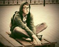 Los jóvenes tristes forman al hombre del inconformista que se sienta en la acera en calle de la ciudad Fotografía de archivo libre de regalías