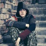 Los jóvenes tristes forman al hombre del inconformista que se sienta en los pasos Imagen de archivo libre de regalías