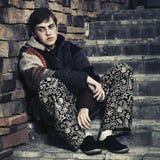 Los jóvenes tristes forman al hombre del inconformista que se sienta en los pasos Foto de archivo