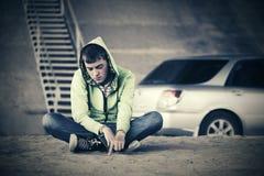 Los jóvenes tristes forman al muchacho que se sienta en la tierra al lado del coche Foto de archivo libre de regalías