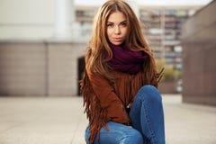 Los jóvenes tristes forman a la mujer en la chaqueta de cuero en la calle de la ciudad Imagenes de archivo