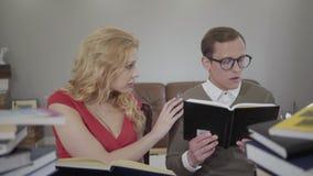 Los jóvenes vistieron modesto al hombre en los vidrios y la mujer rubia rizada que leían el libro que se sentaba en el sofá El ca metrajes
