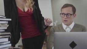 Los jóvenes vistieron modesto al hombre que se sentaba en la tabla que trabajaba en el ordenador portátil La mujer caliente con e metrajes