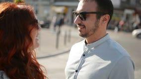 Los j?venes juntan llevar a cabo las manos mientras que caminan abajo de una calle de la ciudad juntos que hablan y que sonr?en almacen de video