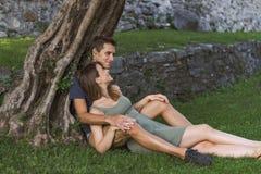 Los j?venes se juntan en el amor que se sienta debajo de un ?rbol en un castillo foto de archivo