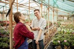 Los jardineros del individuo y de la muchacha en sombreros de una paja se colocan en invernadero en un día soleado imagen de archivo libre de regalías