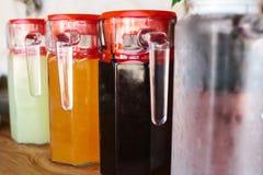 Los jarros de cristal con la variedad de bebidas de la fruta y de la baya con las tapas rojas se colocan en la tabla Foto de archivo libre de regalías