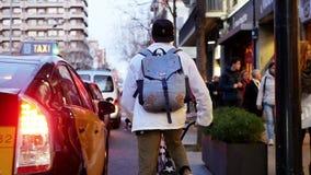 Los jinetes frescos de la bici de los individuos montan a lo largo del camino estrecho con los coches en ciudad ocupada grande de almacen de metraje de vídeo