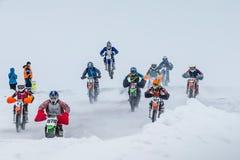 Los jinetes jovenes del grupo en las motocicletas están conduciendo la pista nevada del motocrós imagen de archivo