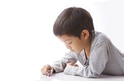 Los juegos concentrados del muchacho cortan en cuadritos en la tabla Imagen de archivo libre de regalías