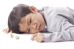 Los juegos concentrados del muchacho cortan en cuadritos en la tabla Foto de archivo libre de regalías