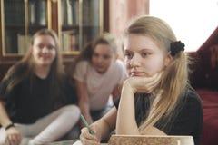 Los juegos de los adolescentes de las muchachas y previenen para hacer lecciones Imágenes de archivo libres de regalías