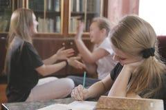 Los juegos de los adolescentes de las muchachas y previenen para hacer lecciones Fotos de archivo