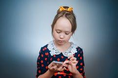 Los juegos de la muchacha con el teléfono blanco Imagenes de archivo