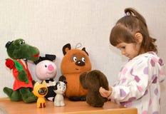 Los juegos de la niña con el Cheburashka Imágenes de archivo libres de regalías