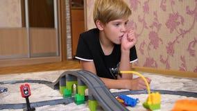 Los juegos de niños con el ferrocarril del ` s de los niños Un adolescente en la sala de juegos, jugando con un sistema de la con metrajes