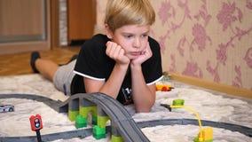 Los juegos de niños con el ferrocarril del ` s de los niños Un adolescente en la sala de juegos, jugando con un sistema de la con almacen de video