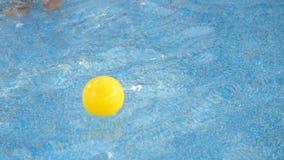 Los juegos de niños con una pequeña bola amarilla en la piscina, capturas él en el agua Primer almacen de video