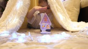 Los juegos de niños en el cuarto de niños en una tienda con una luz de la Navidad Niñez feliz metrajes